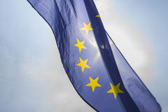 Flag of European Union. Sun shining throuhg, sky in the background Stock Photography