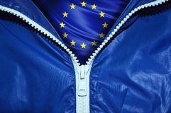 Flag of the European Union under a blue unpacked zipper. Flag of the European Union under unpacked zipper royalty free stock images