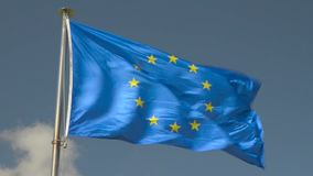 Flag of the European Union waving in the wind over a blue sky stock video