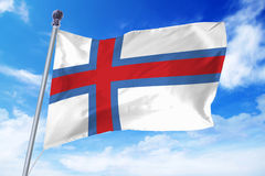 Flag of Faroe islands developing against a clear blue sky Stock Photography