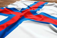 Flag of Faroe Islands on a wooden desk background. Silk Faroese flag top view.  stock photo