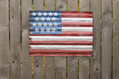 Flag on a Fence. A primitive style American flag painted on a piece of galvanized siding hangs on a wooden fence Royalty Free Stock Photography