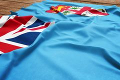 Flag of Fiji on a wooden desk background. Silk Fijian flag top view.  stock images