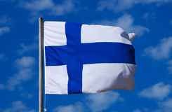 Flag of Finland. The national flag of Finland with a blue cross on white background waving in the wind in front of blue sky background Stock Image