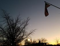 Good night - Small town sunset with tree silhouettes and two American Flags stock photography