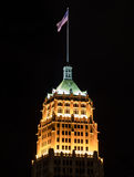 Flag Flies Above the Tower Life Building at Night. San Antonio, United States: January 21st, 2017: Flag flies above the Tower Life Building in San Antonio at Stock Images