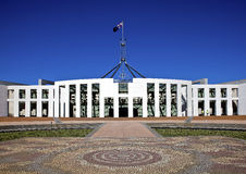 Flag flies on giant flagpole over Australian Parli. Flag flies over Parliament House, Canberra, the seat of government in Australia with Aboriginal mosaic in Royalty Free Stock Photography