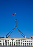 Flag flies on giant flagpole over Australian Parli Stock Photography