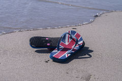 Flag flip flop thongs on a beach Royalty Free Stock Photo
