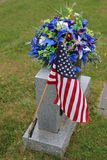Flag and flowers on headstone. Veteran's cemetery headstone decorated with American flag and blue and white flowers Royalty Free Stock Photography