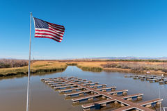 Flag flying over a boat dock Royalty Free Stock Photo