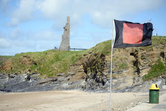 Flag flying beside surf school. Quicksilver flag flying beside surf school with ballybunion castle in background Royalty Free Stock Photos
