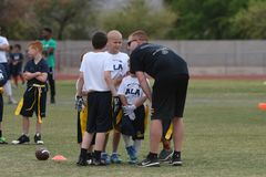 Flag Football Coaching. Flag Football coach teaching the kids how and what to do on the next play Royalty Free Stock Image
