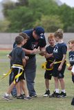 Flag Football Coaching. Flag Football coach teaching the kids how and what to do on the next play Stock Images