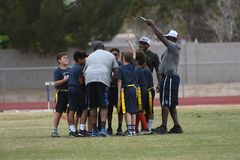 Flag Football Coaching. Flag Football coach teaching the kids how and what to do on the next play Stock Photo