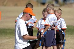 Flag Football. Coach teaching the kids how and what to do on the next play Stock Photography