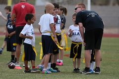 Flag Football Coaching. Flag Football coach teaching the kids how and what to do on the next play Royalty Free Stock Images