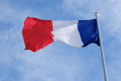 Flag of France on flagpole. Against the blue sky Royalty Free Stock Image