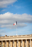 Flag of France fluttering under a serene blue sky Stock Image