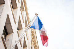 Flag of France fluttering under a serene blue sky Stock Photo