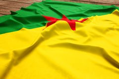 Flag of French Guiana on a wooden desk background. Silk flag top view.  royalty free stock photos