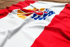 Flag of French Polynesia on a wooden desk background. Silk flag top view.  royalty free stock images