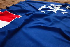 Flag of French Southern and Antarctic Lands on a wooden desk background. Silk flag top view.  stock photos