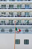 Flag in front of a cruise ship in Costa Maya. Mexican flag flying in front of the upper decks of a cruise ship moored at the pier of the cruise ship terminal in stock photo