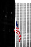 Flag in front of modern skyscraper. An American flag stands in front of the modern facade and exterior wall of a skyscraper with symmetrically arranged windows Stock Photos