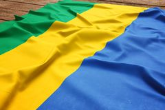 Flag of Gabon on a wooden desk background. Silk Gabonese flag top view.  royalty free stock images