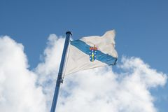 Flag of Galicia waving on the sky royalty free stock photography