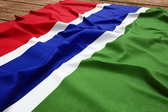 Flag of Gambia on a wooden desk background. Silk Gambian flag top view.  royalty free stock images
