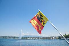 Flag of the Geneva Canton in the city center of Geneva, on the Leman lake. The iconic Jet d`Eau Water Jet can be seen Stock Photography