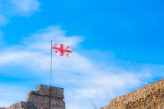 Flag of Georgia on a background of blue cloudy sky royalty free stock image