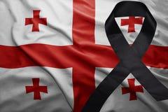Flag of georgia with black mourning ribbon. Waving national flag of georgia with black mourning ribbon Royalty Free Stock Photo