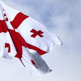Flag of Georgia. Waving on wind and cloudy sky. Close-up view royalty free stock photo