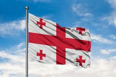 Flag of Georgia waving in the wind against white cloudy blue sky. Georgian flag.  royalty free stock photo