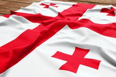 Flag of Georgia on a wooden desk background. Silk Georgian flag top view.  royalty free stock photo