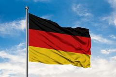 Flag of Germany waving in the wind against white cloudy blue sky. German flag royalty free stock photo
