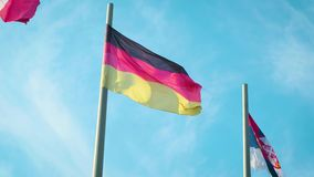 Flag of Germany waving in the wind in front of blue sky.  stock footage
