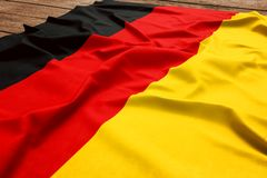 Flag of Germany on a wooden desk background. Silk German flag top view.  stock image