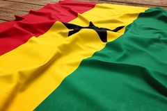 Flag of Ghana on a wooden desk background. Silk Ghanaian flag top view.  stock photo