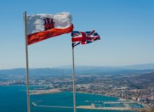 The flag of Gibraltar and the Union Jack flying at the top of the Rock of Gibraltar royalty free stock photography