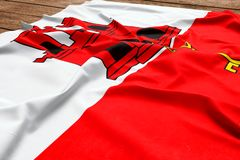 Flag of Gibraltar on a wooden desk background. Silk flag top view.  royalty free stock image
