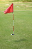 Flag on golf course. A ball close to a hole and a flag on putting green Stock Photo