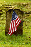 Flag and Grave. An American flag is placed in front of the old gravestone of a soldier Stock Images