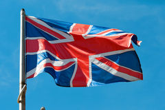 Flag of Great Britain. Waving in the wind against a blue sky Stock Photography