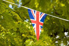Flag of Great Britain with trees in the background. Union jack with green trees in the background Royalty Free Stock Images