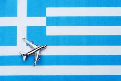 Flag of Greece and the plane. The concept of travel. Toy airplane on the flag of Greece Stock Photos