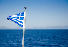 Flag of Greece waving over blue sea waters Royalty Free Stock Photos